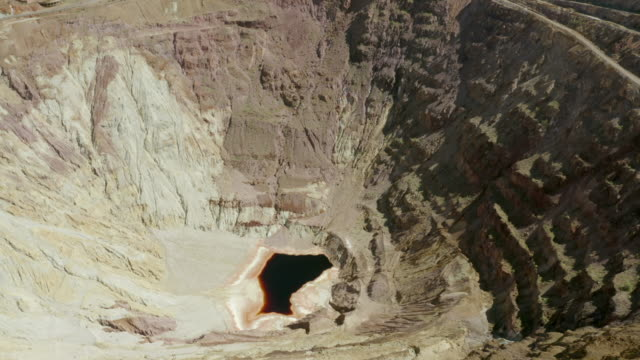 aerial tilt down shot of dirty water pond at abandoned copper mine, drone flying over open-pit quarry on sunny day - bisbee, arizona - imperfection stock videos & royalty-free footage