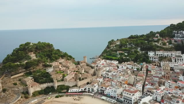 aerial tilt down shot of famous castle in city by sea against sky, drone flying forward over houses - tossa de mar, spain - fortress stock videos & royalty-free footage