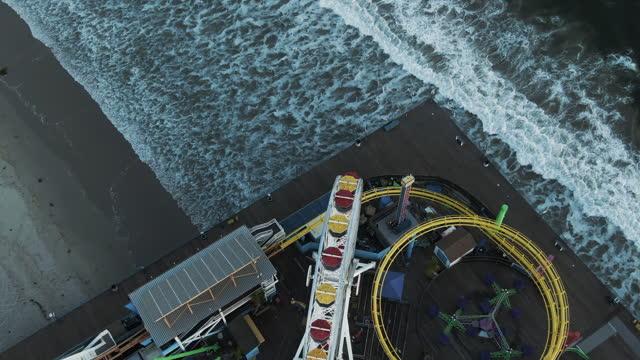 aerial tilt down shot of famous santa monica pier over coastline, drone flying forward over landmark at beach - wildlife stock videos & royalty-free footage