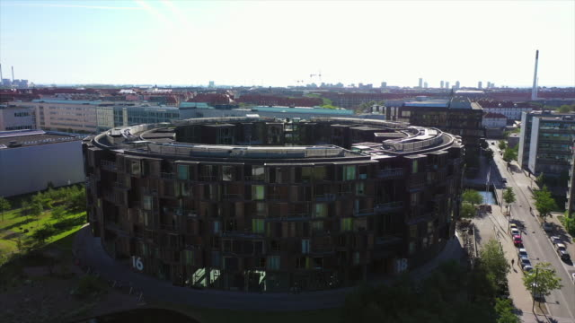 aerial tilt down shot of modern residential college building in city, drone ascending over street with vehicles on sunny day - copenhagen, denmark - copenhagen stock videos & royalty-free footage