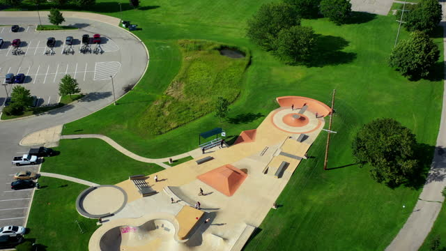 aerial tilt down shot of people at skateboarding park by parking lot, drone flying forward on sunny day - lake geneva, wisconsin - ウィスコンシン州点の映像素材/bロール