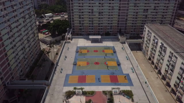 vidéos et rushes de aerial tilt down shot of people at sports venue amidst buildings in city, drone flying forward towards structures on sunny day - hong kong, china - terrain de jeu