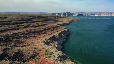 aerial tilt down shot of rocky cliffs at famous reservoir against sky, drone flying forward towards mountains on sunny day - lake powell, arizona - lake powell stock videos & royalty-free footage