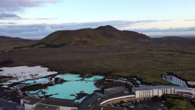 vídeos de stock e filmes b-roll de aerial tilt down shot of tourists enjoying in lagoon during sunset, drone flying over people in famous geothermal spa - blue lagoon, iceland - quinta de saúde