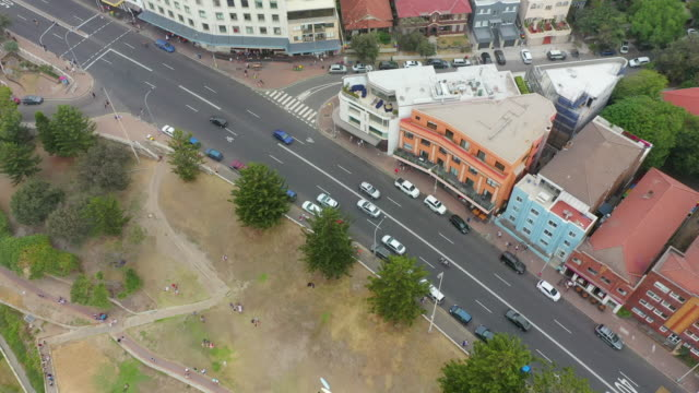 aerial tilt down shot of vehicles on street by buildings in city, drone flying over people on grass by traffic - sydney, australia - urban road stock videos & royalty-free footage