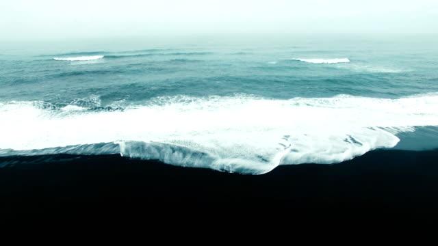 aerial tilt down video of waves on black sand beach - black sand stock videos & royalty-free footage