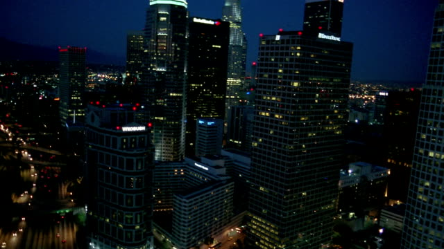 Aerial tilt down view of freeway and skyscrapers at night / Los Angeles