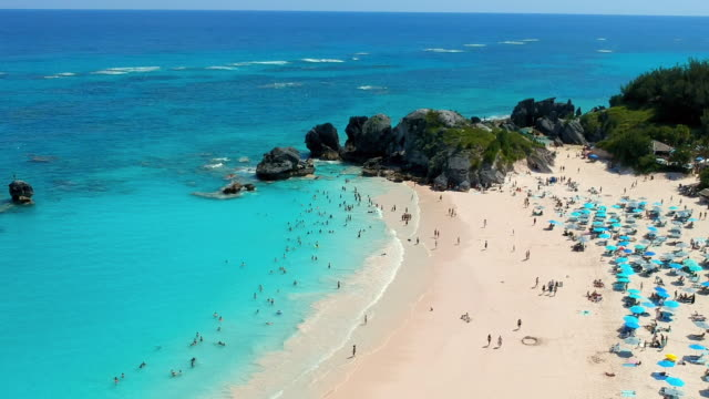 aerial tilt downward: smooth sand of bermuda beach visited by tourist in spanish point, bermuda - bermuda stock videos & royalty-free footage
