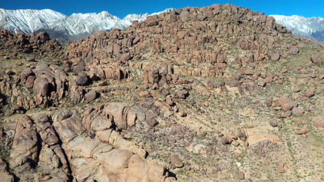 aerial tilt: tall rocky hill with distant snow capped mountains on sunny day - alabama hills, california - hügelkette stock-videos und b-roll-filmmaterial