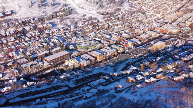 aerial tilt up above residential neighborhood in a snowy mountain ski town with quiet streets and bright morning sunlight - park city, utah - ユタ州 パークシティ点の映像素材/bロール