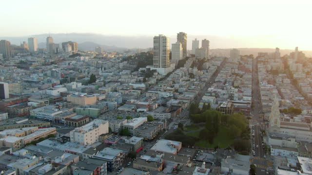 stockvideo's en b-roll-footage met aerial tilt up from a lush neighborhood park to reveal crowded city rooftops and urban skyline against a background of rolling hills and a setting sun - san francisco, california - gekanteld
