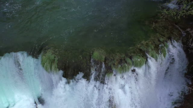 vidéos et rushes de aerial tilt up shot of beautiful cascade splashing in forest against sky, drone flying backwards from waterfall amidst trees - krka, croatia - devant derrière