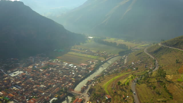 aerial tilt up shot of buildings and river in valley amidst mountains, drone flying over vehicles on street during sunny day - cusco, peru - sunny video stock e b–roll