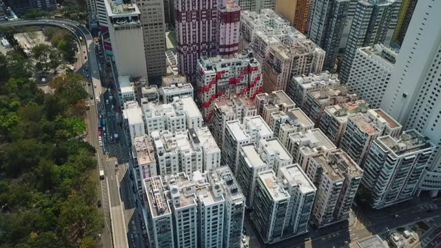 aerial tilt up shot of buildings by vehicles on street in modern city, drone flying forward over cityscape on sunny day - hong kong, china - tilt stock videos & royalty-free footage