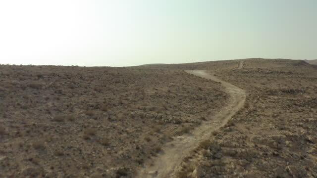 aerial tilt up shot of empty track amidst bushes on mountain, drone flying forward over semi-arid desert against sky - negev, israel - öde landschaft stock-videos und b-roll-filmmaterial