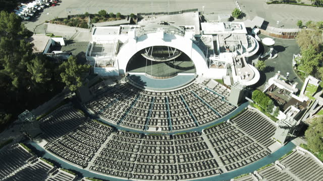 aerial tilt up shot of hollywood bowl by parking lot on sunny day, drone flying over amphitheater - los angeles, california - amphitheatre stock videos & royalty-free footage
