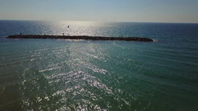 aerial tilt up shot of rocks in sea against blue sky on sunny day, drone flying over ocean - tel aviv, israel - good posture stock videos & royalty-free footage