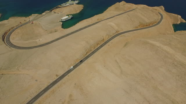 aerial tilt up shot of vehicles on road near sea with ships against sky, drone flying over arid landscape on sunny day - pag, croatia - island stock videos & royalty-free footage