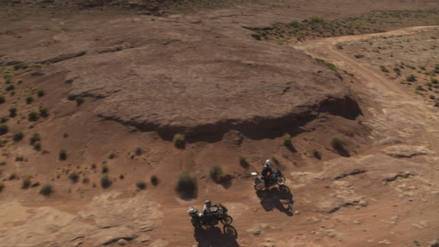 vídeos y material grabado en eventos de stock de aerial tilt up tracking shot of adventure motorcycles riding on dirt road / moab, utah, united states - moab utah
