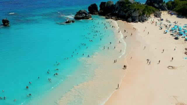 aerial tilt upward backward: swimming and sunbathing at the beach of bermuda in spanish point, bermuda - bermuda stock videos & royalty-free footage