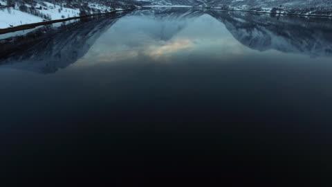 aerial tilt upward: lake at the foot of the mountains of lofoten norway - lofoten, norway - kameralutning bildbanksvideor och videomaterial från bakom kulisserna