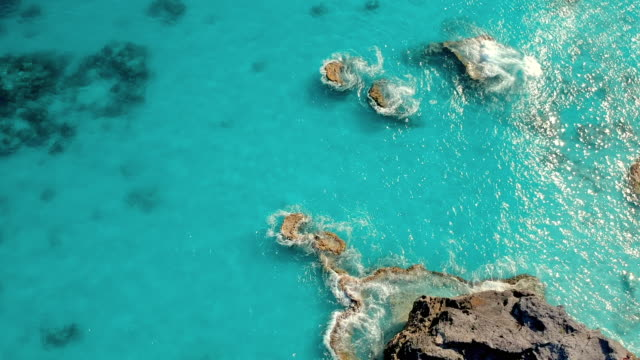 aerial tilt upward slow: the waters of bermuda calmly flowing to the sea in spanish point, bermuda - shallow stock videos and b-roll footage