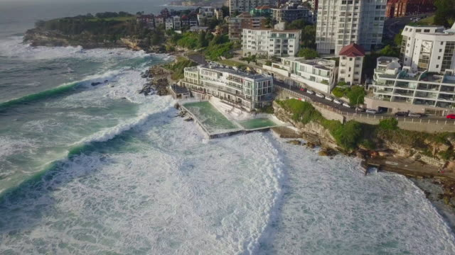 aerial tilt-down: luxurious architecture right by the ocean, bondi beach, australia - panning stock videos & royalty-free footage
