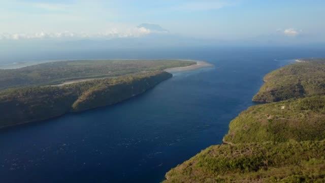 aerial tilt-down: stunning blue strait between lush green islands - stretto video stock e b–roll