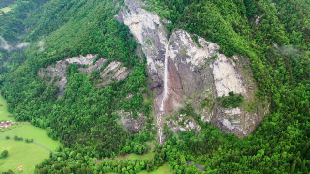 aerial tilt-down: thin waterfall among lush green on stunning mountain over picturesque town - chamonix, france - thin stock videos & royalty-free footage