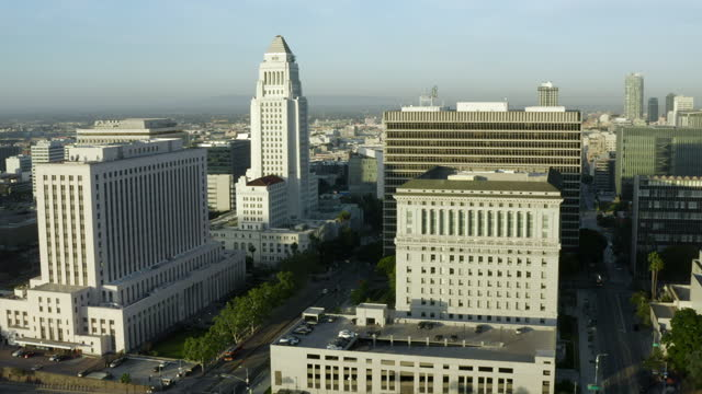 aerial tilting up and away from la city hall and surrounding government buildings under a bright sky with the city suburbs stretching into the distant horizon - los angeles, california - courthouse stock videos & royalty-free footage