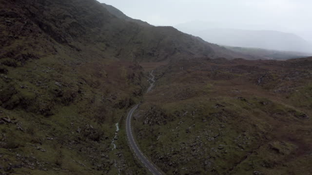 Aerial Tilt-up: Black Car Driving Among Scenic Mountains in Kerry, Ireland