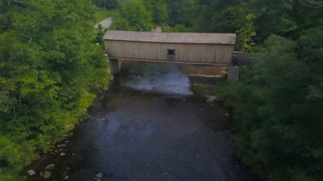 aerial tilt-up: covered bridge over salmon river among lush green - woodland stock videos & royalty-free footage