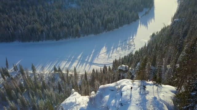 aerial tilt-up: man standing on ledge over frozen river in usva, russia - pinaceae stock videos & royalty-free footage