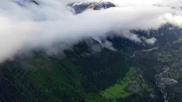 aerial tilt-up: picturesque village in cloudy valley under sunlit mountains - mount blanc, france - tornspira bildbanksvideor och videomaterial från bakom kulisserna