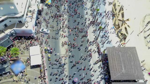 aerial tilt-up: pride parade on scenic promenade along beautiful seashore, tel aviv, israel - pride stock videos & royalty-free footage