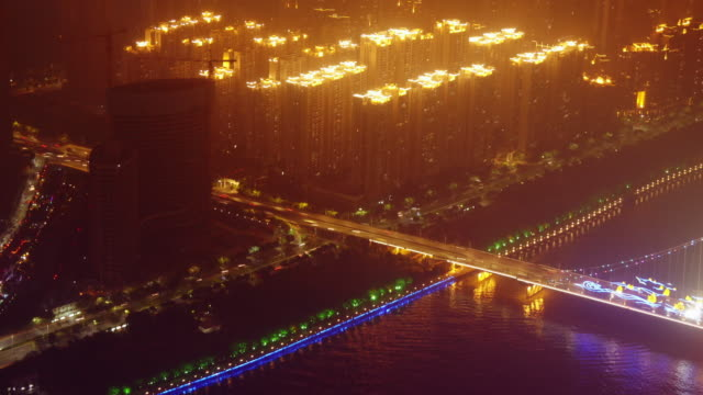 aerial time lapse at night of illuminated scyscraper rooftops next to  liede bridge in guangzhou, china. - spoonfilm stock-videos und b-roll-filmmaterial