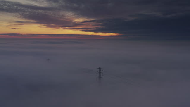 aerial time lapse at sunset showing an electricity pylon surrounded by freezing fog, england, united kingdom - sustainable energy stock videos & royalty-free footage