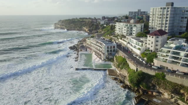 vídeos de stock, filmes e b-roll de aerial time lapse: luxurious structure right by the ocean, bondi beach, australia - praia de bondi