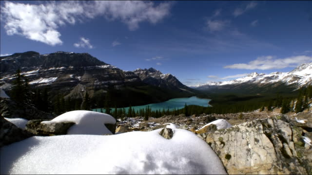 vídeos de stock, filmes e b-roll de aerial time lapse over snowy rocks in banff national park with mountains in background/ alberta, canada - alberta