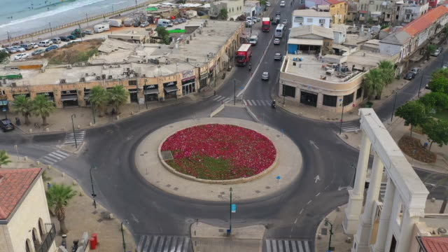 aerial time lapse shot of vehicles at roundabout in coastal city, drone panning over street - jaffa, israel - ジャファ点の映像素材/bロール