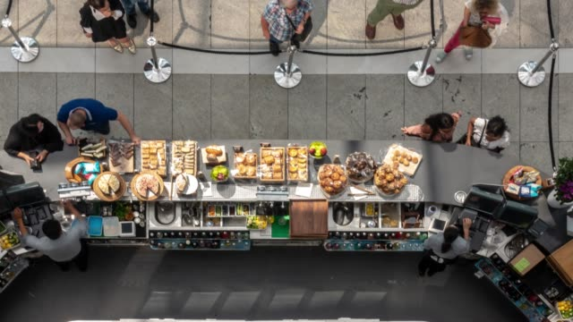 time-lapse aereo: il cliente acquista cibo dal chiosco bar in caffetteria - bar video stock e b–roll