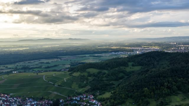 aerial timelapse of an old town and forest at sunset near freiburg - horizontal stock-videos und b-roll-filmmaterial