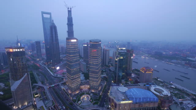 aerial timelapse shanghai - day to night  from pearl towerpudong, huangpu river, jin mao tower, shanghai international finance centre, shanghai world financial center, day to night, skyline, city lights, streets, traffic,  china - spoonfilm stock-videos und b-roll-filmmaterial