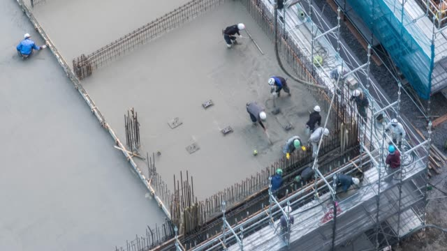 aerial time-lapse: working in construction site in tokyo - concrete stock videos & royalty-free footage