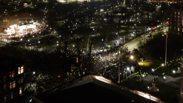 stockvideo's en b-roll-footage met aerial tl of anti-racism demonstration in front of state house in boston during christmas tree lighting ceremony - racisme