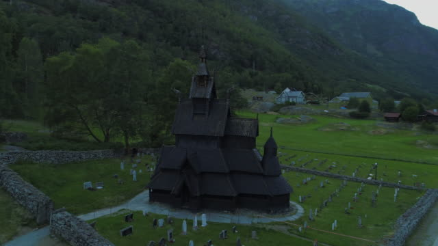 aerial: tombstones surrounding traditional wooden kaupanger stave church in valley - 囲む点の映像素材/bロール