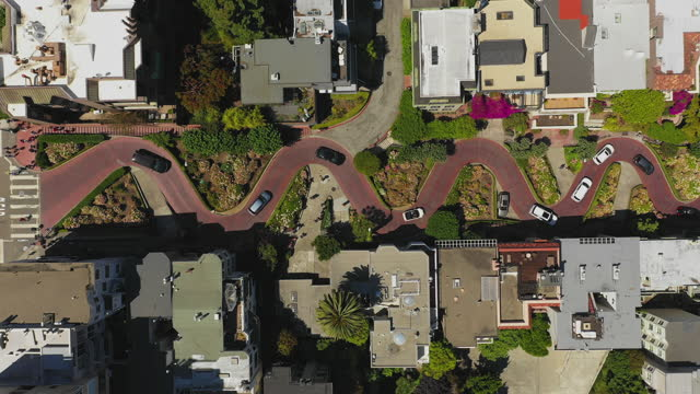 aerial top ascend shot of vehicles on zigzag street amidst buildings, drone flying over city on sunny day - san francisco, california - zigzag stock videos & royalty-free footage