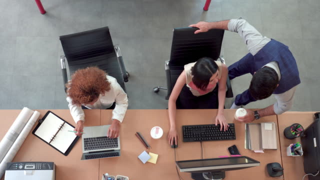 aerial top down shot of busy corporate modern office with rows off multi-ethnic businesswomen working on desktop computer and laptop, manager discussing and determining colleague 's work. concept of leadership and corporate business. - table top shot video stock e b–roll