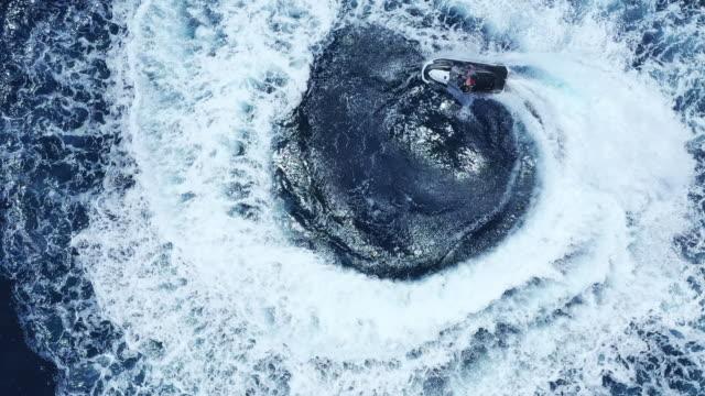 vista aerea dall'alto verso il basso dell'uomo moto d'acqua in cerchio - acquascooter video stock e b–roll