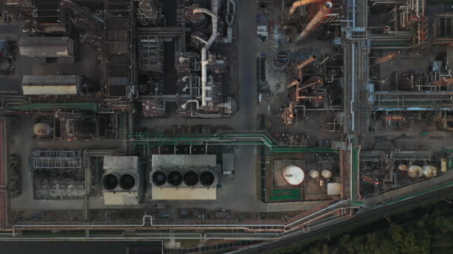 aerial top down view over oil refinery or chemical factory and power plant with many storage tanks and pipelines. - ölindustrie stock-videos und b-roll-filmmaterial